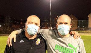 Två spelare i herrlaget som håller om varandra efter träningen med munskydd på.