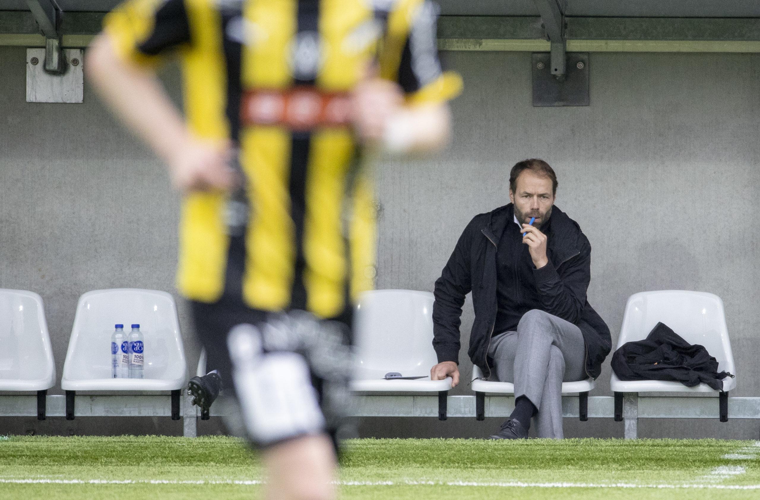 Andreas Alm sitter på tränarbänken och tittar på när BK Häcken spelar match.