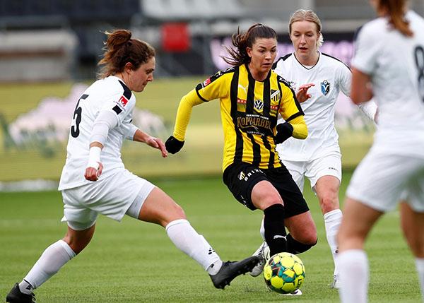 Pauline Hammarlund tar bollen i duell med flera spelare.