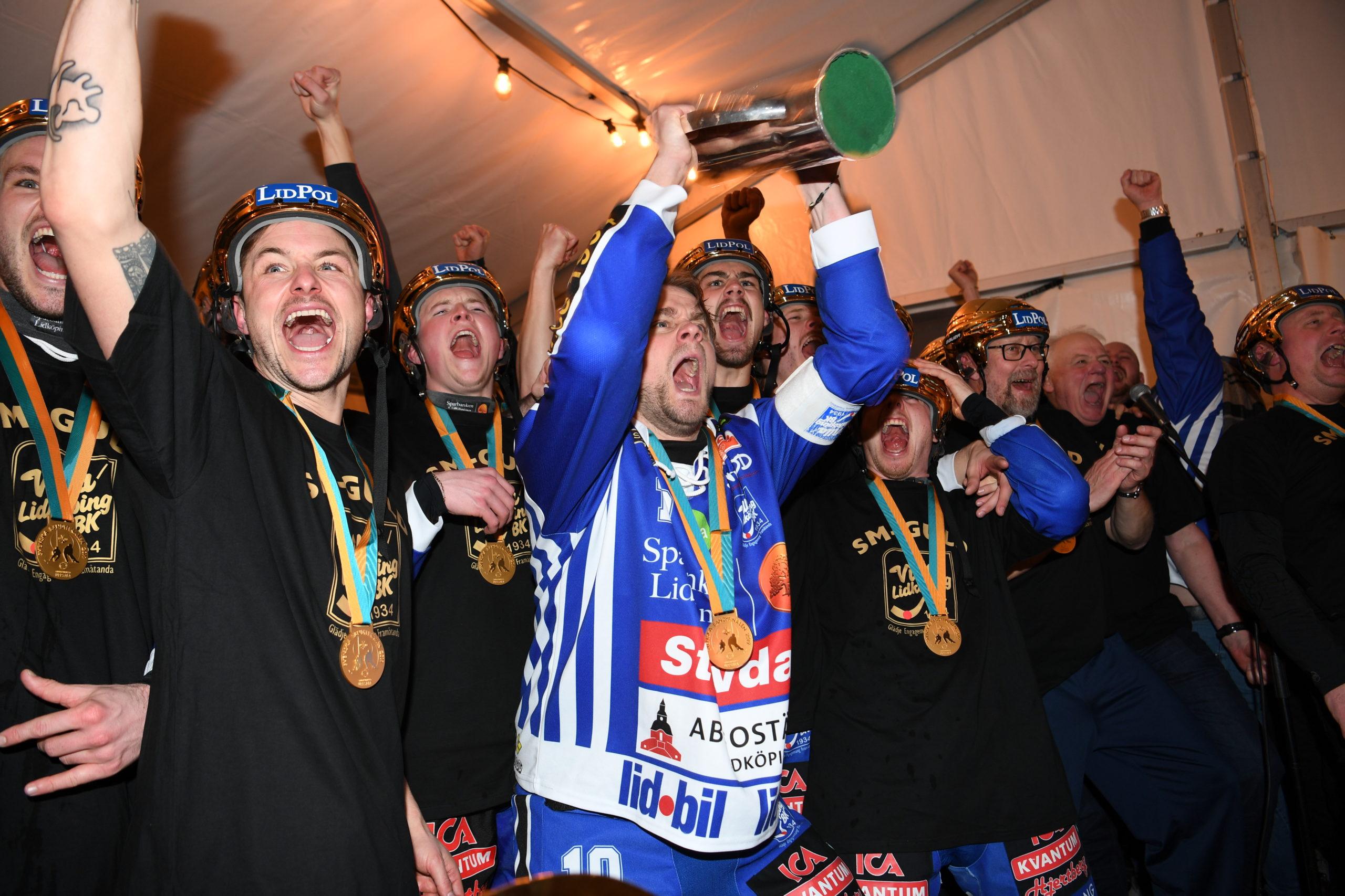 Villa Lidköpings spelare lyfter pokalen i omklädningsrummet.