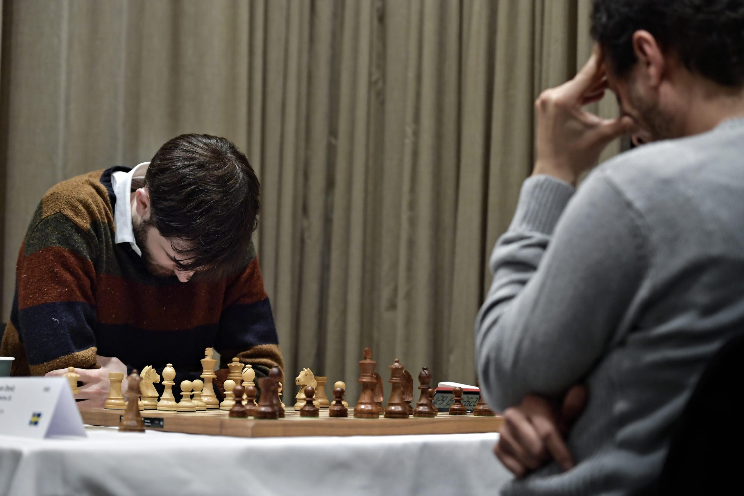 Två män spelar schack. Båda hänger ned med huvudena. En har på sig en randig tröja med gult, rött, blått och grönt. Den andra har på sig en grå tröja