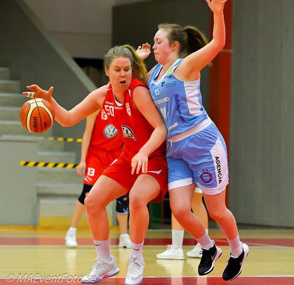 Två basketspelare i kamp om bollen i en närduell.