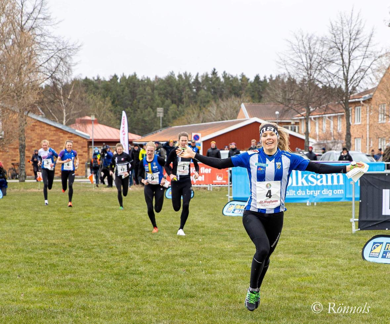 Sara Hagström sträcker ut armarna när hon springer i mål på orienterings SM.