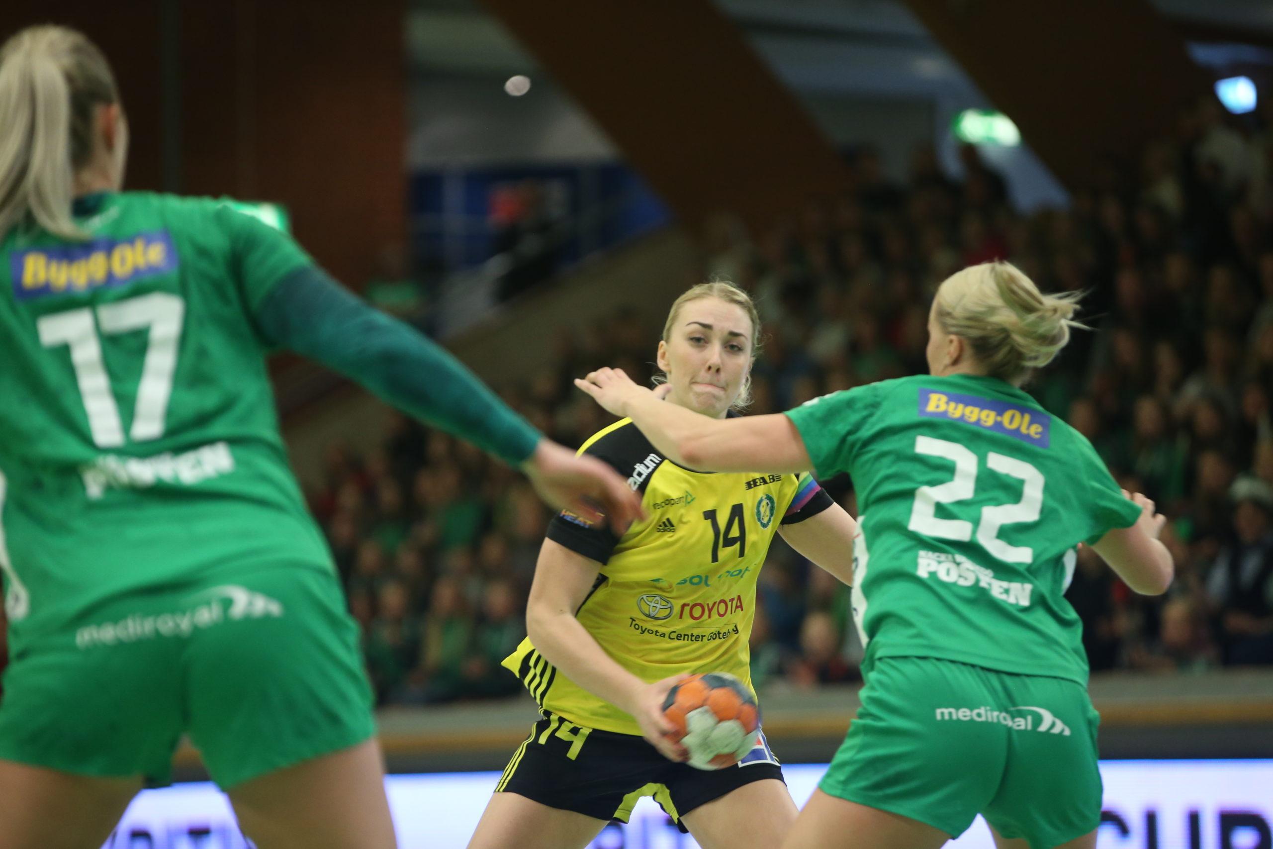 Handsbolls match. En tjej I gul och svart matchtröja blir försvarad av två tjejer i gröna matchställ.