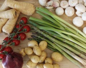 Potatis, champinjoner, palsternacka, sparris, tomater, rödlök och vårlök på skärbräda.