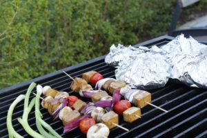 Grillspett, vårlök och folieknyten på grill med grön bakgrund.