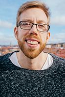 Foto på Mikael Mide. Han har rött hår, glasögon och grå tröja.