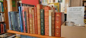 Gamla böcker med fina bokryggar på en hylla.
