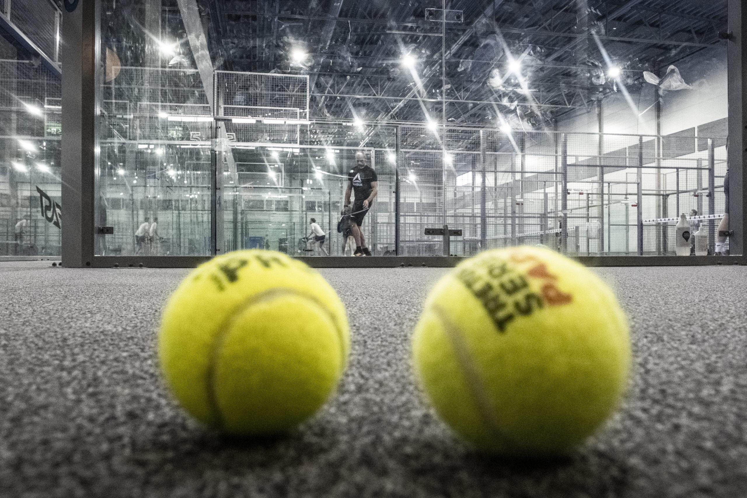 Två tennisbollar på golvet i en padelhall. Bakom syns en man som spelar.